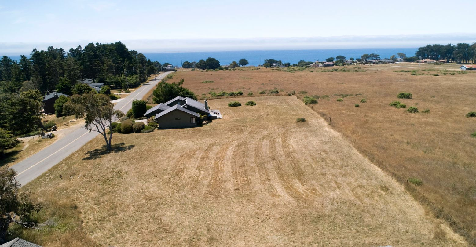 Aerial view of house surrounded by grassy brown lawn with ocean in background